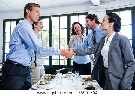 Business colleagues shaking hands after a successful lunch meeting at restaurant