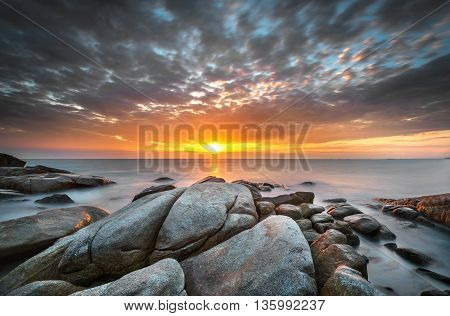Beautiful sunset at tropical rocks and beach