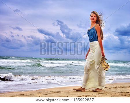 Summer girl sea. Woman goes on coast.