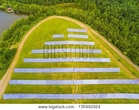 Aerial view to solar power plant in rural landscape. Industrial background on renewable resources theme.