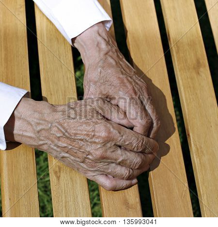 The palms of wrinkled hands of an elderly man on a background of wooden planks