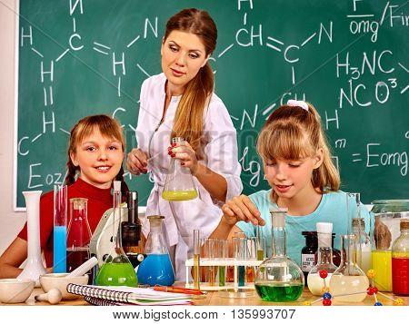 Children girl and chemistry teacher holding chemistry flask in chemistry class.