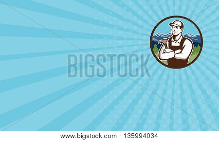 Business card showing illustration of a carpenter builder wearing hat holding hammer with arms crossed looking to the side viewed from front set inside circle with mountains in the background done in retro style.