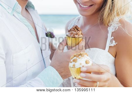 Couple eating cupcakes in their wedding at the beach
