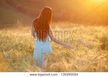 woman in blue dress walking on wheat field