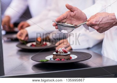 Close-up of chef finishing a dessert plate with icing sugar in the kitchen