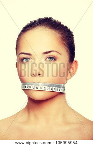 Woman with a white measuring tape covering the mouth