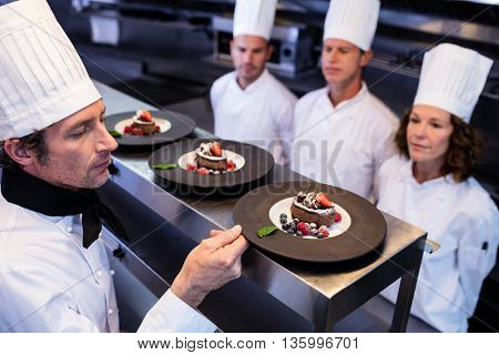 Head chef inspecting dessert plates at order station in restaurant