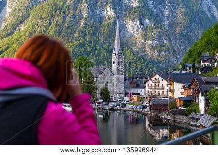 Woman  taking photo of stunning lake and Hallstatt view