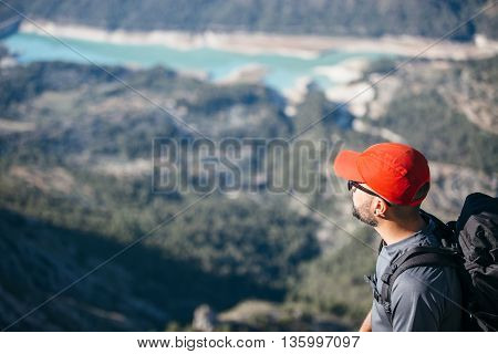Side view of adult backpacker against of sunny landscape