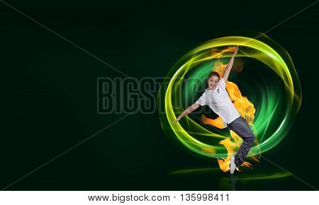 Young woman hip hop dancer with fire effect at background
