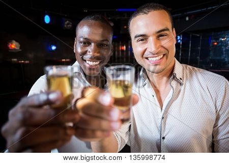 Handsome men drinking together in night club