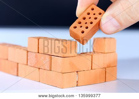 put in the last brick on a brick wall