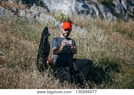 Portait of bearded climber making shot wth cell phone while sitting on grass