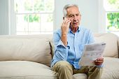 Old man reading document while talking on phone in living room at home poster