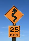 picture of mph  - old twisty road sign with 25 mph warning in yellow and black on blue sky background - JPG