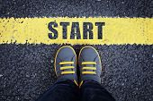 Start line child in sneakers standing next to a yellow starting line poster