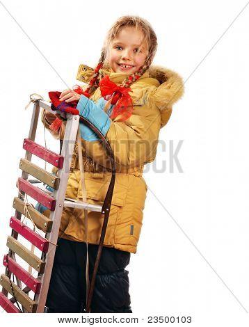 Little girl holding sleigh on white.