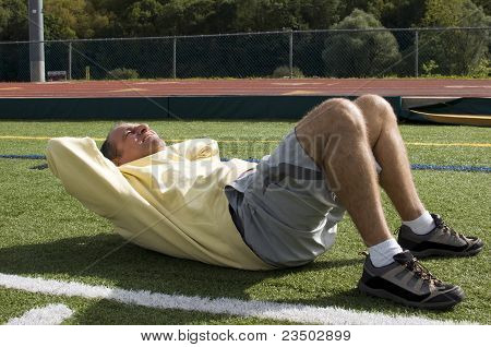 Middle Age Senior Man Exercising Sit Ups Ab Exercise On Sports Field