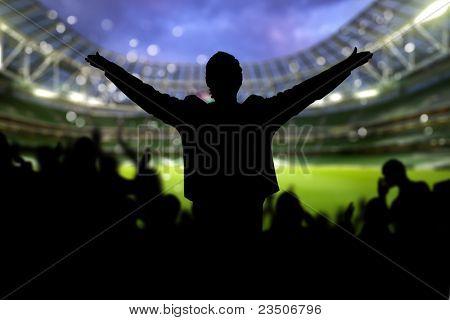 Imagen de un estadio lleno con siluetas de fan en primer plano