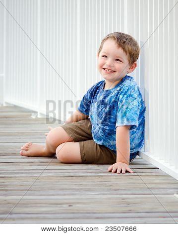 Portrait Of Happy Young Boy On Beach Boardwalk