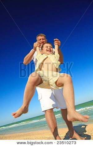 A happy boy tossed into the blue sky by his father at beach