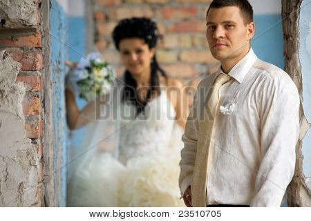 Wedding couple posing at old grunge place and brick wall