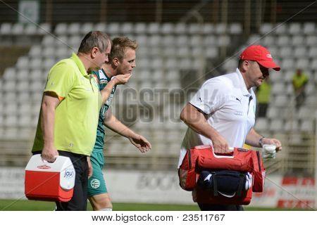 KAPOSVAR, HUNGARY - SEPTEMBER 10: Unidentified player is injured at a Hungarian National Championship soccer game - Kaposvar (white) vs Gyor (green) on September 10, 2011 in Kaposvar, Hungary.
