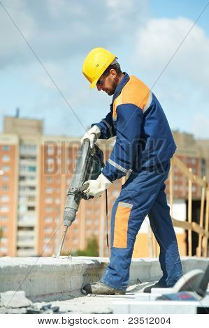Portarait of positive Builder worker with pneumatic hammer drill equipment at construction site