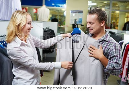 Young couple choosing business suit shirt and necktie during clothing shopping at sales store