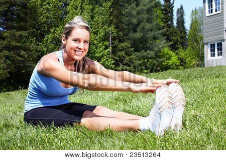 Young woman doing yoga in park. Healty lifestyle.