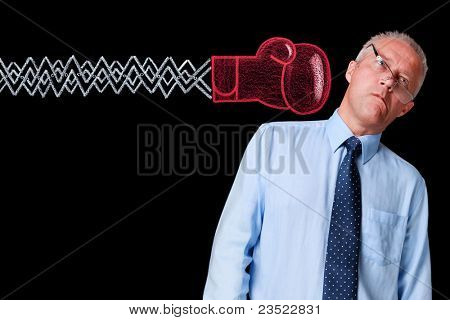 Photo of a mature businessman against a black background being delivered a knockout punch by a handrawn chalk boxing glove on expanding mechanical arm.
