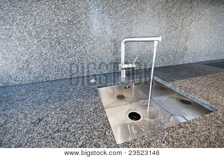 modern rectangular stainless steel kitchen sink on a granite worktop