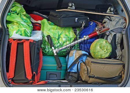 Carro muito com o tronco cheio de bagagem pronta para a partida da família férias