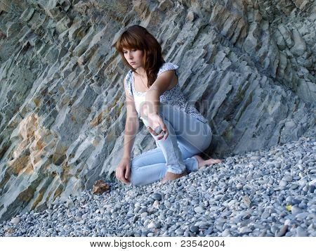 The sad lonely girl sits on a beach near a rock