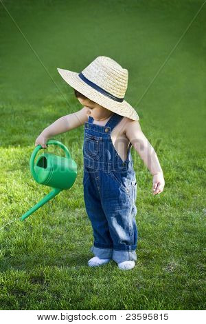 little baby gardener lost in the moment with the sun shinning in his face while he works hard