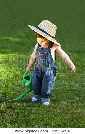sweet little baby gardener caught in the moment while working hard in his garden whith his big hat on