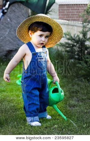 pequeño bebé jardinero concentrado en su trabajo de regar las plantas