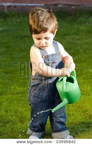 little baby gardener watering the grass and wearing work outfit