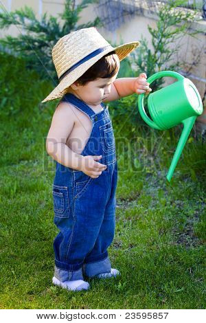 little baby gardener with hat watering the plants