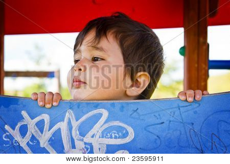 little boy playing hide and seek in the park