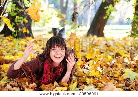 Smiling happy girl, playing with autumn leaves. Outdoor.
