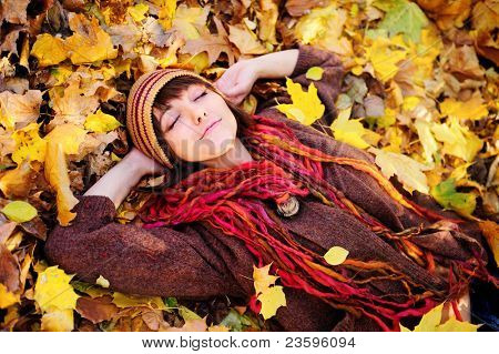 Smiling happy girl portrait, lying in autumn leaves. Outdoor.