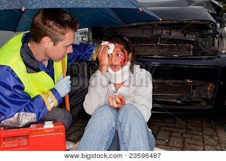 Paramedic caring for an injured woman under an umbrella