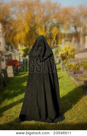 Woman with victorian cape visiting a very old graveyard