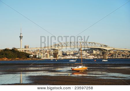 Auckland Harbor bridge, low tide, with city background, New Zealand