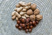 Peanuts, Hazelnuts And Walnuts With Nutshells Mix On Natural Bamboo Mat Surface poster