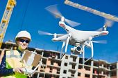 Drone operated by construction female worker on building site poster