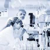 Health Care Researchers Microscoping In Life Science Laboratory. Young Female Research Scientist And poster