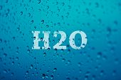foto of h20  - a background made by droplets of water with blue tones and the word  - JPG